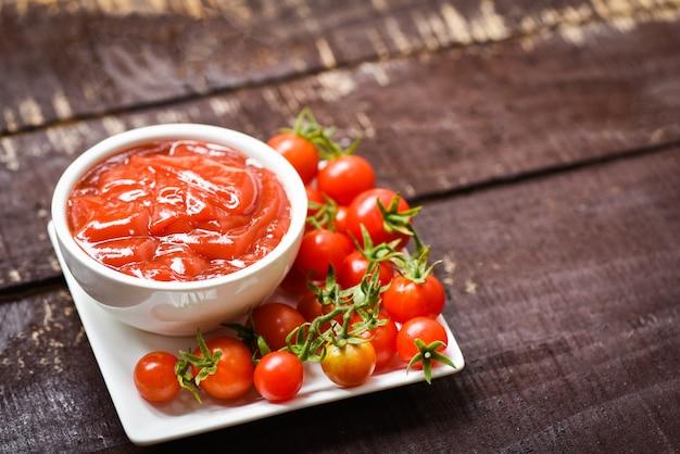 Ketchup dans une tasse et tomates fraîches sur plaque / fermer la sauce tomate sur bois sombre