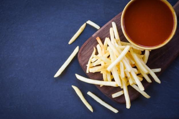Ketchup frites en planche de bois avec fond noir - savoureuses frites de pommes de terre pour la nourriture ou une collation délicieux ingrédients ménagers italiens faits maison