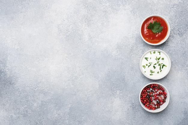 Ketchup mayonnaise verts épices poivre sel dans des assiettes sur une table en béton gris avec copie espace.