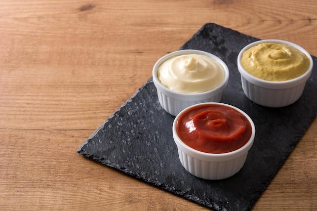 Ketchup, moutarde et mayonnaise dans des bols sur une table en bois
