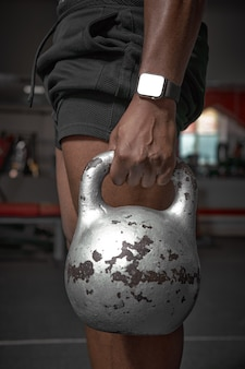 Kettlebell d'argent de sport dans la main d'un gars athlétique afro-américain avec un gars de montres s'entraînant avec