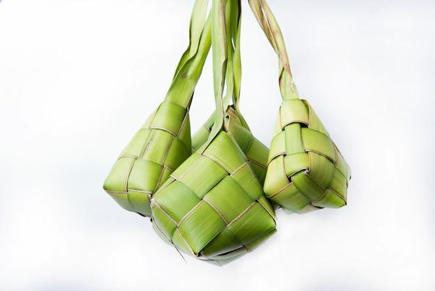 Ketupat (boulette de riz) est un aliment traditionnel de l'indonésie au cours de l'aïd mubarak isolé sur une surface blanche