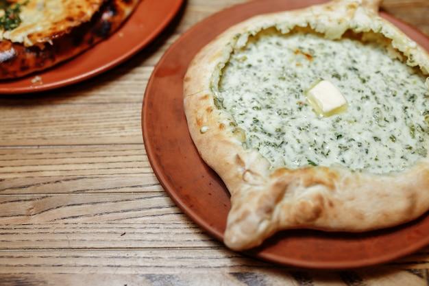 Khachapuri fabriqué à partir d'une délicieuse pâte tendre avec des épinards, du fromage fondu et du beurre en gros plan. hachapuri traditionnel garni de feuilles de spinacia sur fond rustique en bois.
