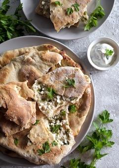 Khachapuri avec fromage cottage et crème sure avec du persil vert dans l'assiette
