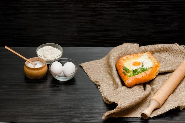 Khachapuri sur un sac, de la farine, des œufs et un rouleau à pâtisserie