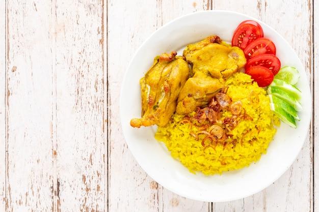 Khao mok gai, version musulmane thaïlandaise du biryani indien, riz jaune parfumé au poulet dans une assiette en céramique blanche sur fond blanc de texture de bois ancien, vue de dessus, poulet biryani, biriani, beriani