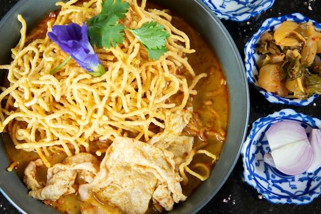Khao soi, soupe de nouilles au curry à la thaïlandaise du nord et sa tranche de porc