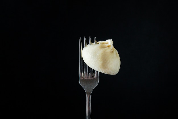 Khinkali avec des boulettes de sauce farcies sur une fourchette