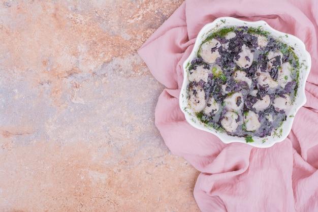 Khinkali caucasien cuit et servi avec des herbes hachées dans un bol blanc.