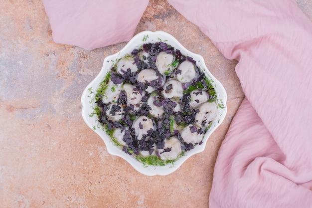 Khinkali caucasien non cuit avec des herbes hachées dans un bol.