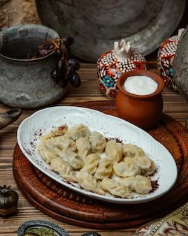 Khinkali géorgien à l'intérieur d'une assiette blanche avec du yaourt.