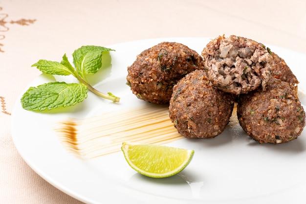 Kibbeh cuit au four sur une assiette blanche de la nourriture arabe