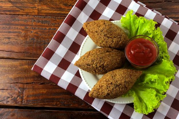Kibbeh frit à la sauce tomate sur une assiette, sur une table en bois rustique