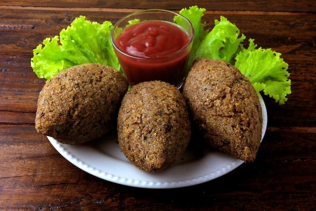 Kibbeh frit à la sauce tomate sur une assiette
