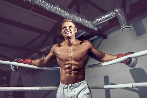 Kick boxer professionnel musclé reposant sur les cordes dans le coin du ring pendant l'entraînement pour le prochain match