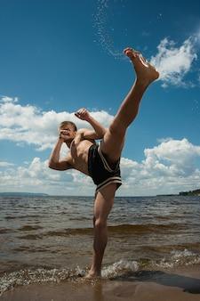 Kickboxer donne un coup de pied en plein air en été contre la mer.