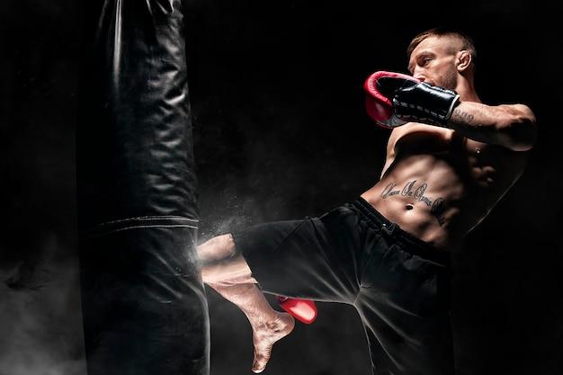 Kickboxer frappe le sac avec son genou. entraîner un athlète professionnel. le concept de mma, lutte, muay thai. technique mixte