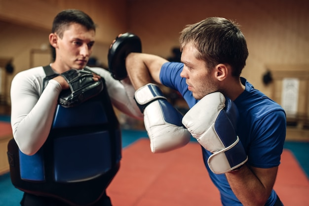 Kickboxer masculin dans les gants pratiquant le coup de coude avec un entraîneur personnel dans les coussinets, entraînement en salle de gym. fighter faisant un puissant coup de poing à l'entraînement, pratique du kickboxing en action
