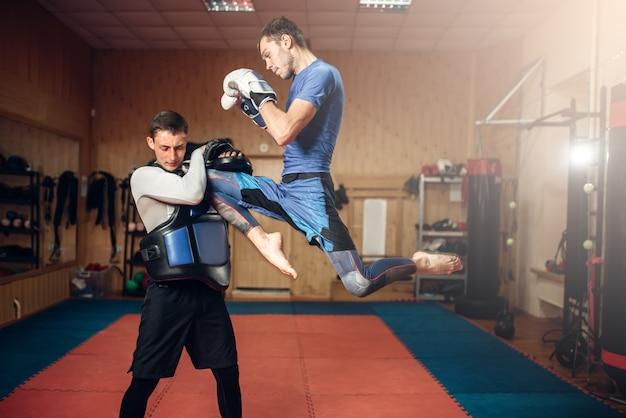 Kickboxer masculin faisant un coup de pied en saut, pratiquant avec un entraîneur personnel, entraînement en salle de gym. boxeur en formation, pratique du kickboxing
