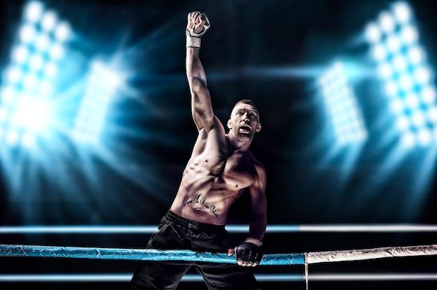 Kickboxer posant sur le ring. l'athlète a grimpé les cordes et a pris une position victorieuse sur fond de projecteurs.