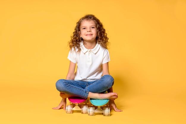 Kid actif et heureux s'amusant avec penny board, planche à roulettes de stand de visage souriant