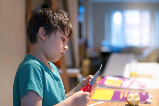 Kid à l'aide de ciseaux coupe du papier blanc