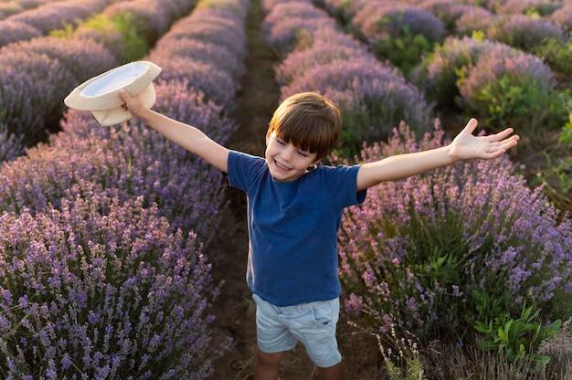 Kid à angle élevé dans le champ de fleurs
