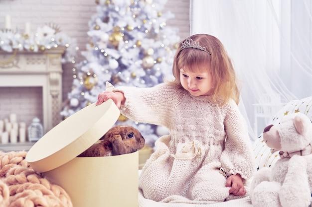 Kid a un animal de compagnie pour noël. la chambre est décorée d'un sapin de noël. enfant heureux ouvre la boîte-cadeau. enchantement et surprise à la surprise.