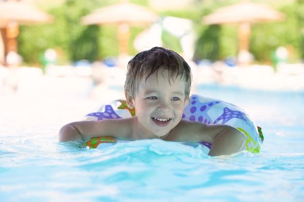 Kid apprend à nager avec un anneau d'eau en plastique