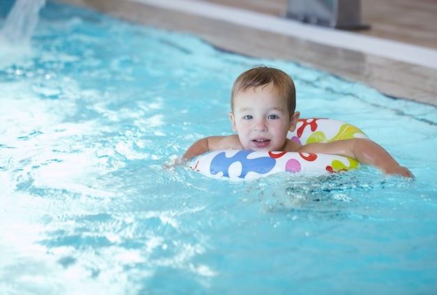 Kid apprend à nager en utilisant un anneau d'eau en plastique