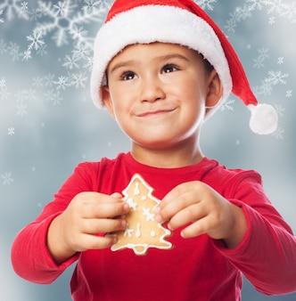 Kid avec un arbre à biscuits dans un fond de flocons de neige