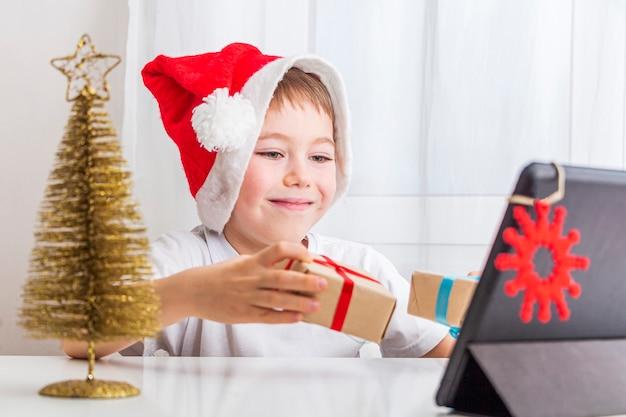 Kid boy célèbre noël en ligne avec un ami ou des grands-parents sur appel vidéo sur tablette