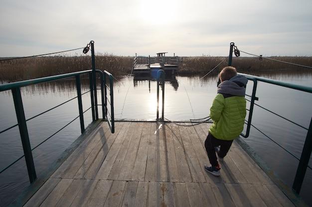 Kid caucasien tirant le bac à travers la rivière