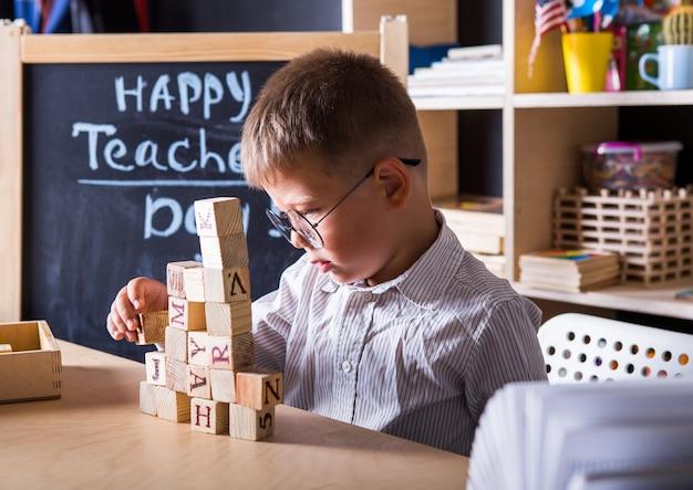 Kid construisant une pyramide de cubes en classe