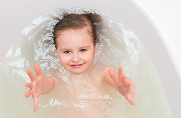Kid dans une baignoire, tendre la main, topshot