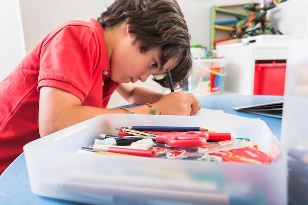 Kid dessin près de la boîte de papeterie