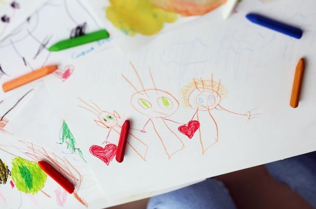 Kid dessine un dessin au crayon de la famille heureuse. dessin d'enfants.