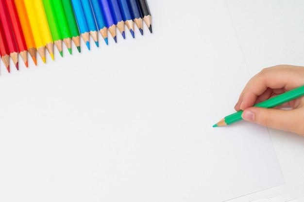 Kid dessine sur du papier blanc vierge.