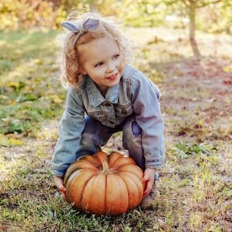Kid enfant fille essayant d'élever une énorme citrouille en plein air. citrouille d'halloween dans la rue d'automne dans les mains des enfants de petite fille blonde caucasienne en costume de denim dans le jardin de la ferme. portrait agrandi carré.