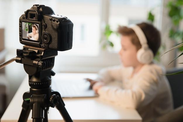 Kid enregistrant son gameplay pour vlog. blogueur vidéo jeune garçon faisant un flux avec ses abonnés. flou artistique.