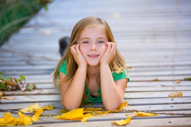 Kid fille en automne bois deck avec feuilles jaunes en plein air