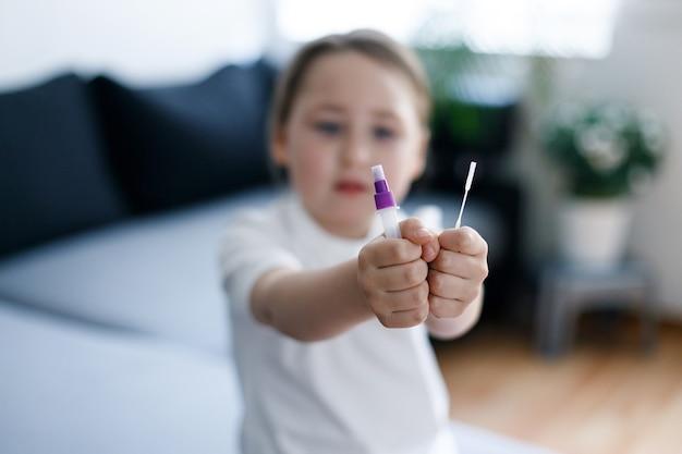 Kid fille avec bandelette de test pour les anticorps ou la maladie à virus sars-cov-2 dans les mains