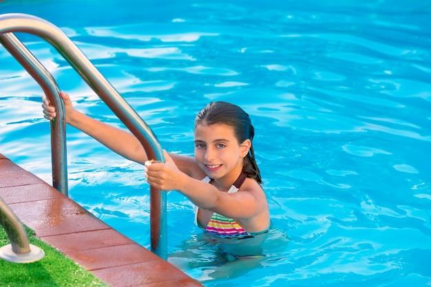 Kid fille dans la piscine pendant les vacances d'été