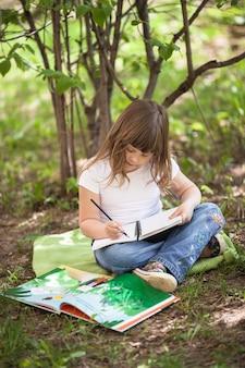 Kid fille écrit dans un cahier, plein air, printemps