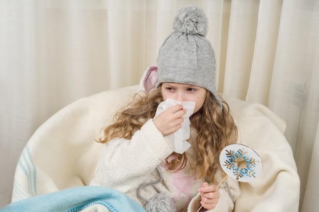 Kid fille éternue dans un mouchoir à la maison