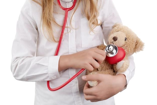 Kid fille jouant au docteur avec peluche comme pépinière