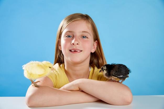 Kid fille avec des poussins jouant sur le bleu