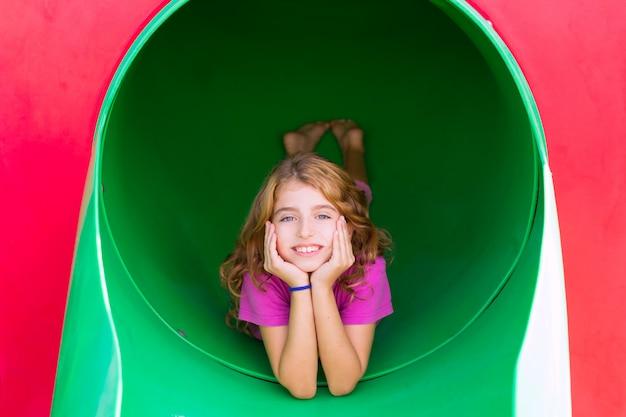 Kid fille souriante dans l'aire de jeux du parc détendue