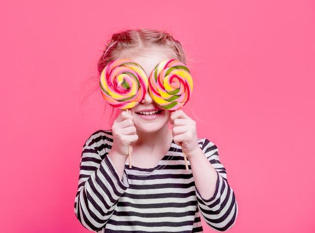 Kid fille avec sucettes devant ses yeux