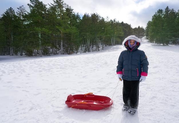Kid fille avec traîneau dans une pente de montagne enneigée